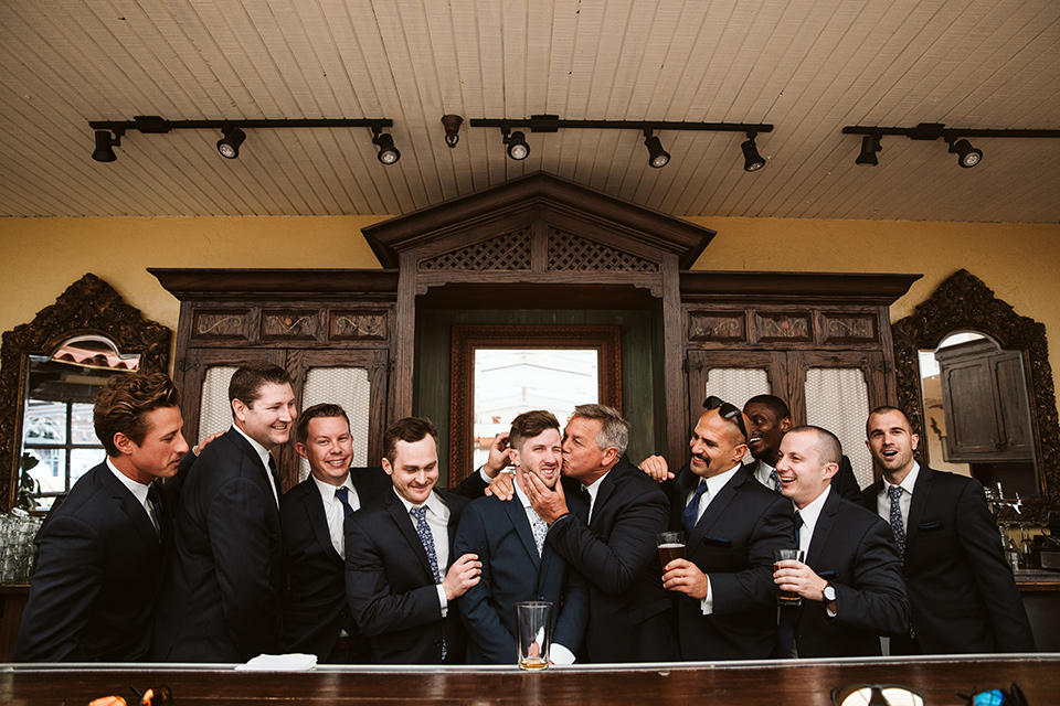 Adobe-de-Capastrano-Amanda-and-Asher-groomsmen-having-a-beer-before-silly-picture-groomsmen-wearing-navy-suits-with-floral-ties-and-brown-shoes-including-the-groom