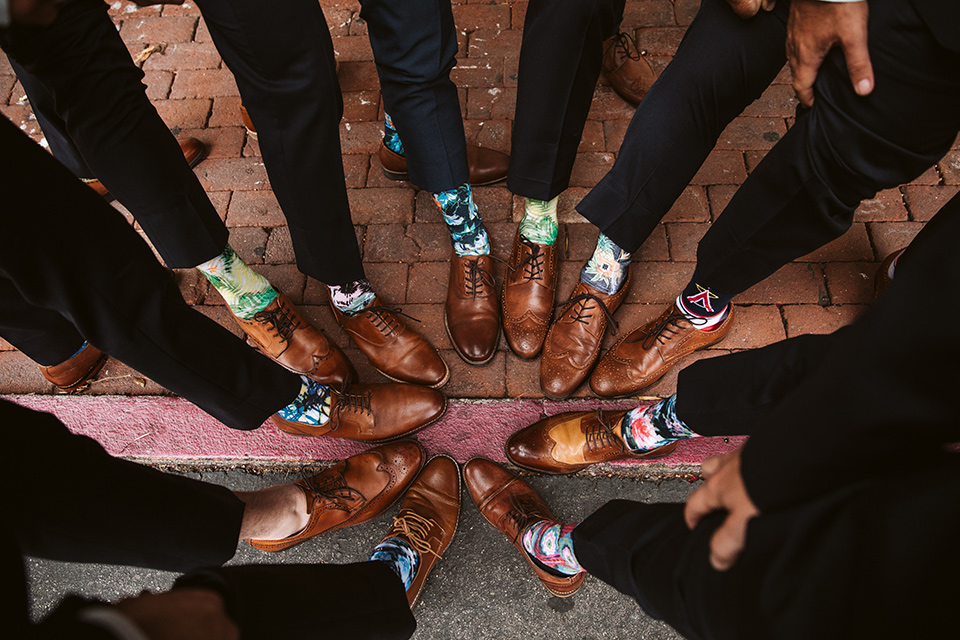 Adobe-de-Capastrano-Amanda-and-Asher-groomsmen-socks-groomsmen-wearing-navy-suits-with-floral-ties-and-brown-shoes-including-the-groom-all-wearing-fun-different-colored-and-printed-socks