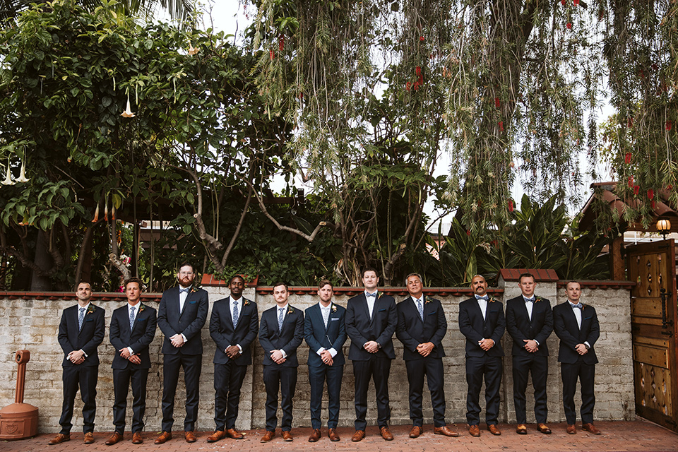 Adobe-de-Capastrano-Amanda-and-Asher-groomsmen-standing-tall-all-in-a-line-groomsmen-wearing-navy-suits-with-floral-ties-and-brown-shoes