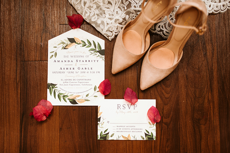 Adobe-de-Capastrano-Amanda-and-Asher-invitations-white-invitations-with-floral-accents-around-the-edge-with-blush-and-nude-toned-heels-with-floating-flowers-as-decor