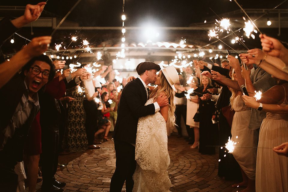 Adobe-de-Capastrano-Amanda-and-Asher-kissing-with-sparkler-send-off-bride-wearing-a-fit-and-flare-lace-gown-with-an-open-back-and-sweetheart-neckline-as-well-as-a-white-wide-brimmed-hat-groom-wearing-navy-suit-with-floral-tie-with-a-paperboy-hat