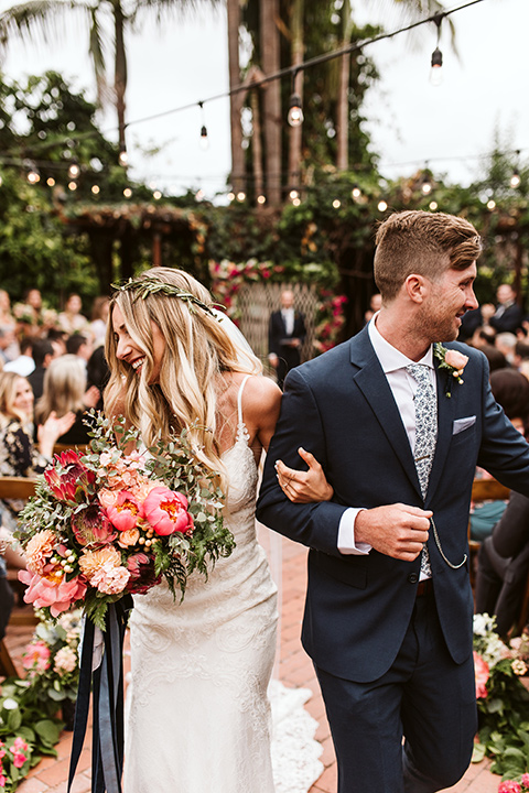 Adobe-de-Capastrano-Amanda-and-Asher-leaving-ceremony-smiling-at-guests-bride-wearing-a-white-lace-fit-and-flare-gown-with-open-back-and-sweetheart-neckline-groom-in-navy-suit-with-blue-and-white-floral-tie-she-is-holding-her-bouquet-with-a-green-floral-crown-on-her-head-with-loose-waves