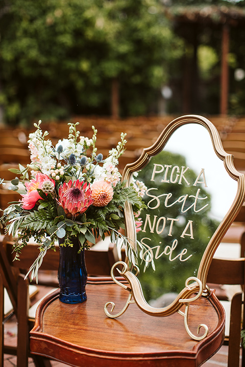 Adobe-de-Capastrano-Amanda-and-Asher-pick-a-seat-décor-ceremony-décor-florals-with-a-painted-antique-mirror-that-says-take-a-seat-not-a-side