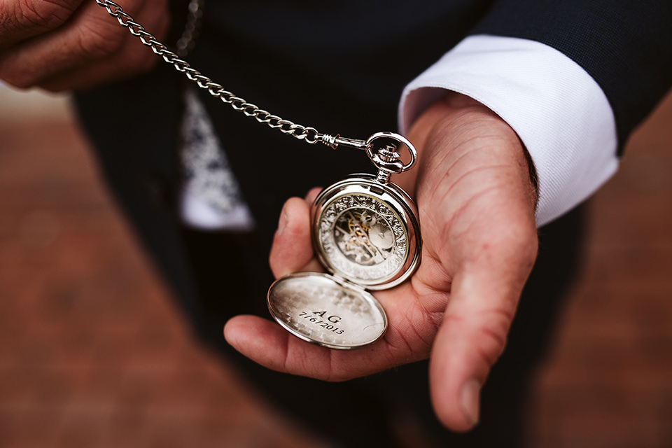 Adobe-de-Capastrano-Amanda-and-Asher-pocketwatch-groom-wearing-a-navy-suit-with-floral-tie-holding-a-pocketwatch-that-is-engraved-with-their-wedding-date