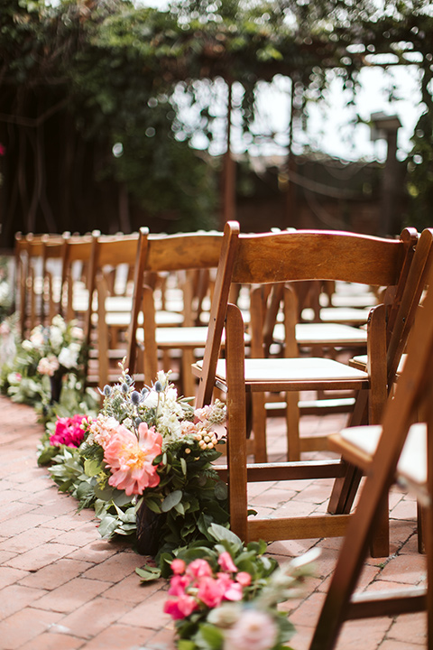 Adobe-de-Capastrano-Amanda-and-Asher-seating-at-ceremony-close-up-on-ceremony-décor-wooden-folding-chairs-with-pink-and-green-lush-florals-linning-the-aisle