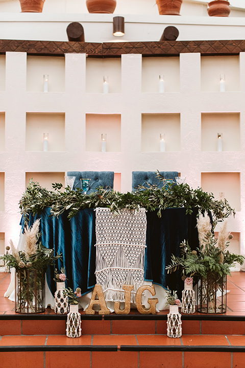 Adobe-de-Capastrano-Amanda-and-Asher-sweetheart-table-sweetheart-table-with-grennery-andblue-velvet-table-linnens-and-candles-on-the-ground