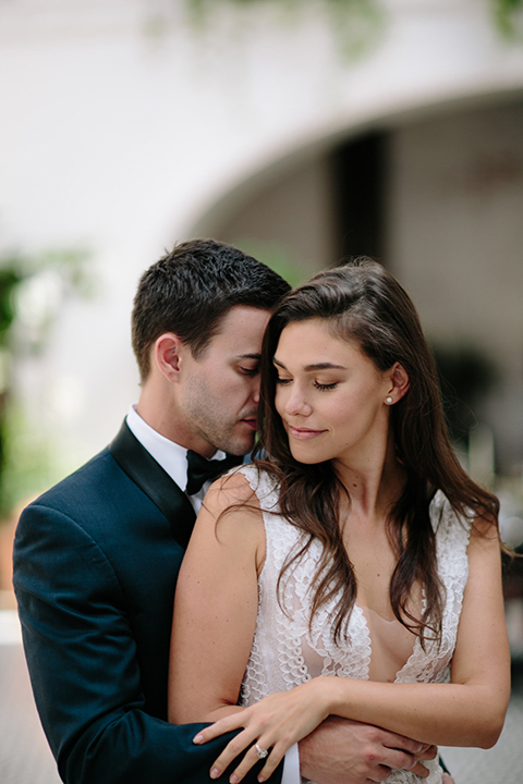 Southern-california-wedding-at-the-ebell-of-long-beach-bride-and-groom-dancing-and-hugging-bride-wearing-a-lace-a-line-dress-with-straps-and-hair-in-loose-down-waves-and-groom-in-navy-tux-with-black-trim-and-black-bowtie
