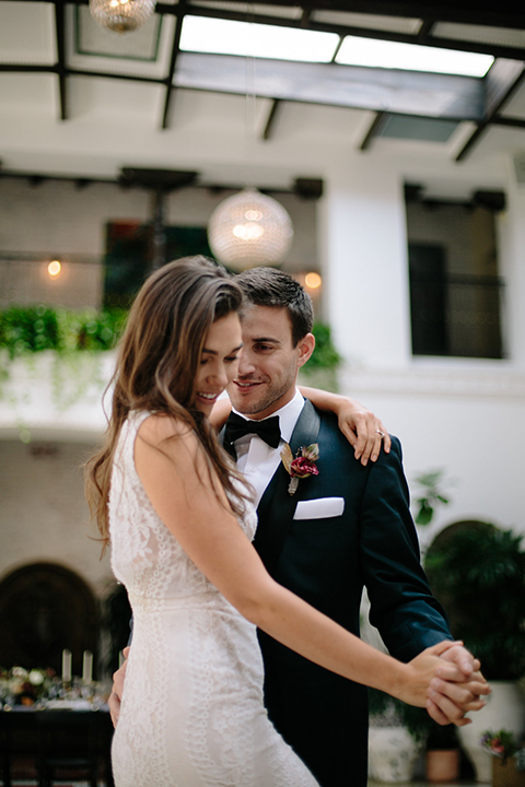 Southern-california-wedding-at-the-ebell-of-long-beach-bride-and-groom-dancing-and-smiling-bride-wearing-a-lace-a-line-dress-with-straps-and-hair-in-loose-down-waves-and-groom-in-navy-tux-with-black-trim-and-black-bowtie