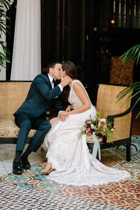 Southern-california-wedding-at-the-ebell-of-long-beach-bride-and-groom-holding-hands-sitting-and-kissing-bride-wearing-a-lace-a-line-dress-with-straps-and-hair-in-loose-down-waves-and-groom-in-navy-tux-with-black-trim-and-black-bowtie