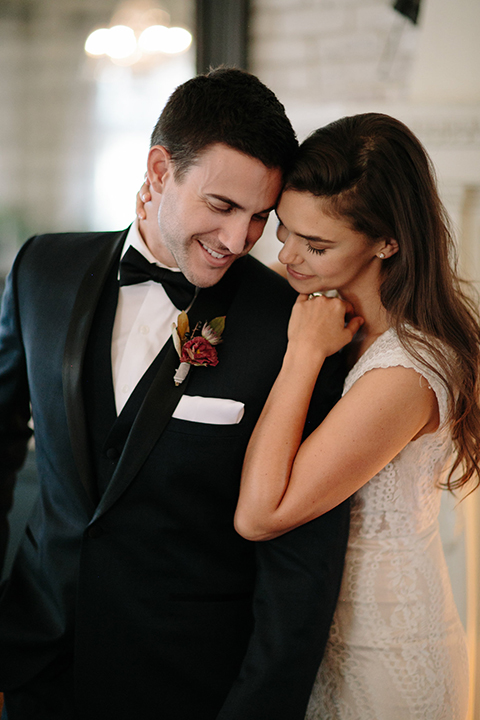 Southern-california-wedding-at-the-ebell-of-long-beach-bride-and-groom-hugging-close-up-bride-wearing-a-lace-a-line-dress-with-straps-and-hair-in-loose-down-waves-and-groom-in-navy-tux-with-black-trim-and-black-bowtie