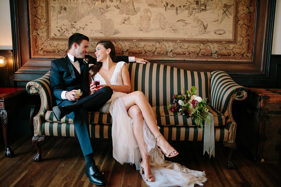Southern-california-wedding-at-the-ebell-of-long-beach-bride-and-groom-sitting-on-couch-bride-wearing-a-lace-a-line-dress-with-straps-and-hair-in-loose-down-waves-and-groom-in-navy-tux-with-black-trim-and-black-bowtie