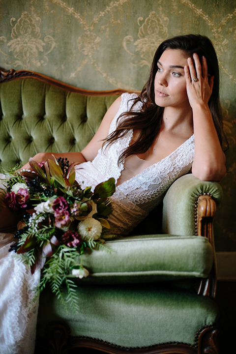 Southern-california-wedding-at-the-ebell-of-long-beach-bride-lace-gown-sitting-with-bouquet-bride-wearing-a-lace-a-line-dress-with-straps-and-hair-in-loose-down-waves-holding-her-bouquet-and-looking-off-to-the-side-and-her-hand-resting-on-her-head