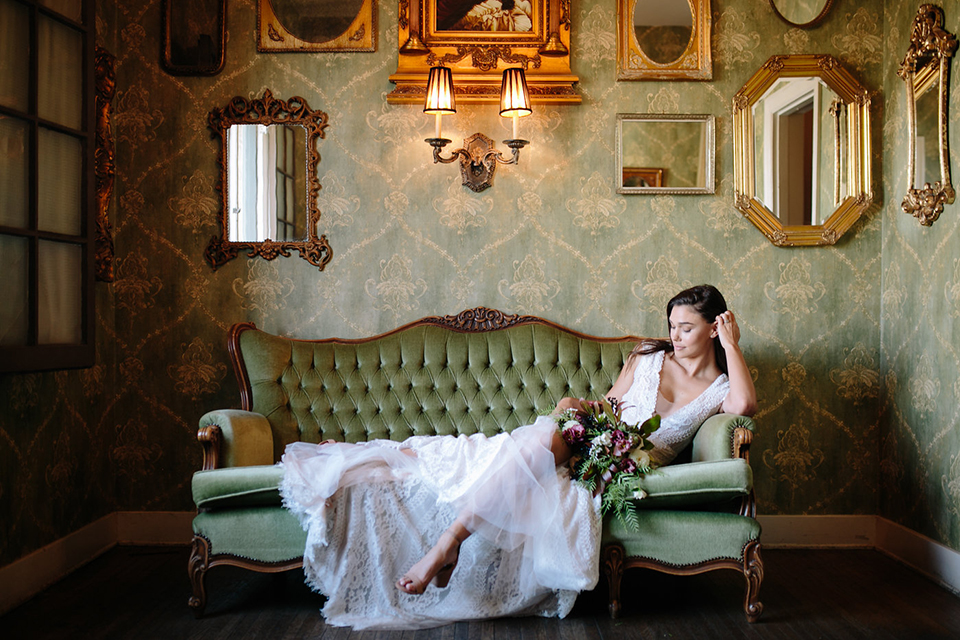 Southern-california-wedding-at-the-ebell-of-long-beach-bride-lace-gown-sitting-bride-wearing-a-lace-a-line-dress-with-straps-and-hair-in-loose-down-waves-holding-her-bouquet-and-her-hand-resting-on-her-head