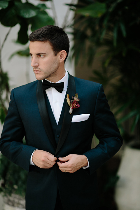 Southern-california-wedding-at-the-ebell-of-long-beach-groom-navy-tuxedo-buttoning-jacket-groom-in-navy-tux-with-black-trim-and-black-bowtie-with-a-white-pocket-square-and-burgundy-boutionniere