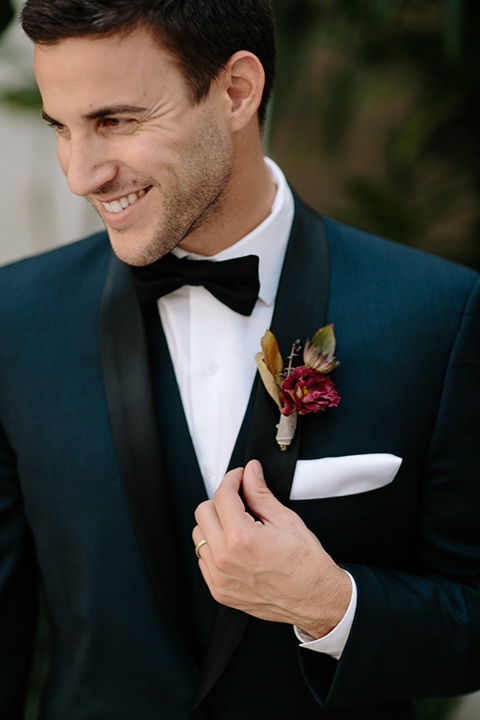 Southern-california-wedding-at-the-ebell-of-long-beach-groom-navy-tuxedo-close-up-groom-in-navy-tux-with-black-trim-and-black-bowtie-with-a-white-pocket-square-and-burgundy-boutionniere