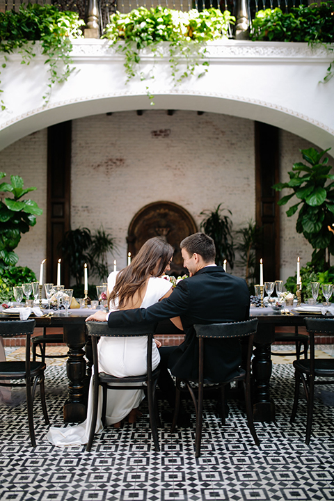 Southern-california-wedding-at-the-ebell-of-long-beach-reception-bride-and-groom-sitting-at-table-bride-wearing-a-lace-a-line-dress-with-straps-and-hair-in-loose-down-waves-and-groom-in-navy-tux-with-black-trim-and-black-bowtie
