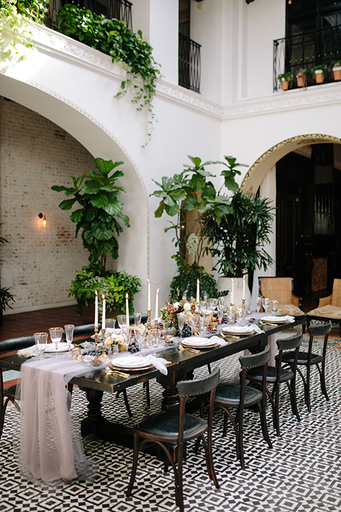 Southern-california-wedding-at-the-ebell-of-long-beach-table-set-up-with-chairs-wooden-chairs-and-table-with-white-and-chamange-toned-linnens-and-greenery-as-floral-arrangements