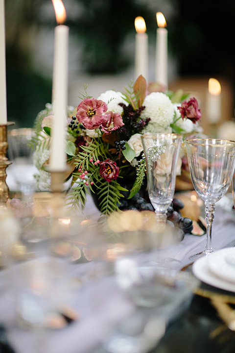 Southern-california-wedding-at-the-ebell-of-long-beach-table-set-up-with-flowers-and-candle-decor-wooden-chairs-and-table-with-white-and-chamange-toned-linnens-and-greenery-as-floral-arrangements