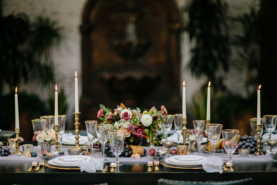 Southern-california-wedding-at-the-ebell-of-long-beach-table-set-up-with-flowers-wooden-table-and-chairs-with-neutral-colored-linneds-and-high-roman-candles-with-green-andwhite-florals