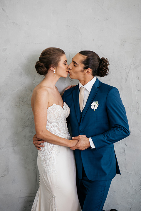 FD-Studios-bride-and-groom-close-by-grey-wall-bride-wearing-a-flowing-strapless-gown-with-a-lace-bodice-groom-in-a-dark-blue-suit-with-a-blush-long-tie