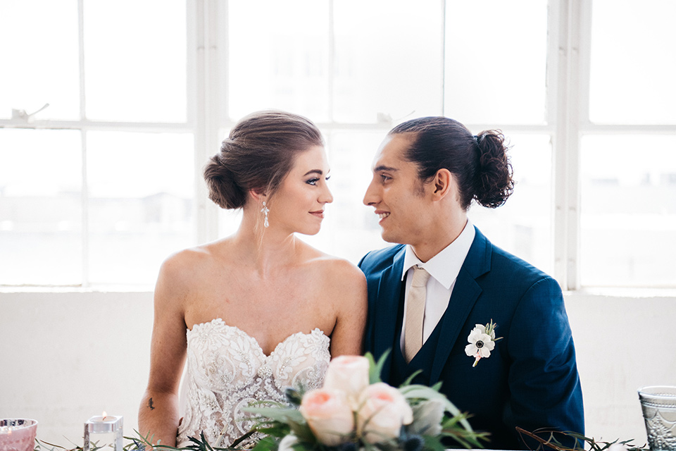 FD-Studios-bride-and-groom-looking-at-each-other-bride-in-a-strapless-flowing-gown-groom-in-a-dark-blue-suit-with-a-blush-long-tie