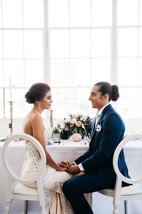FD-Studios-bride-and-groom-sitting-at-table-bride-wearing-a-flowing-strapless-gown-with-a-lace-bodice-groom-in-a-dark-blue-suit-with-a-blush-long-tie