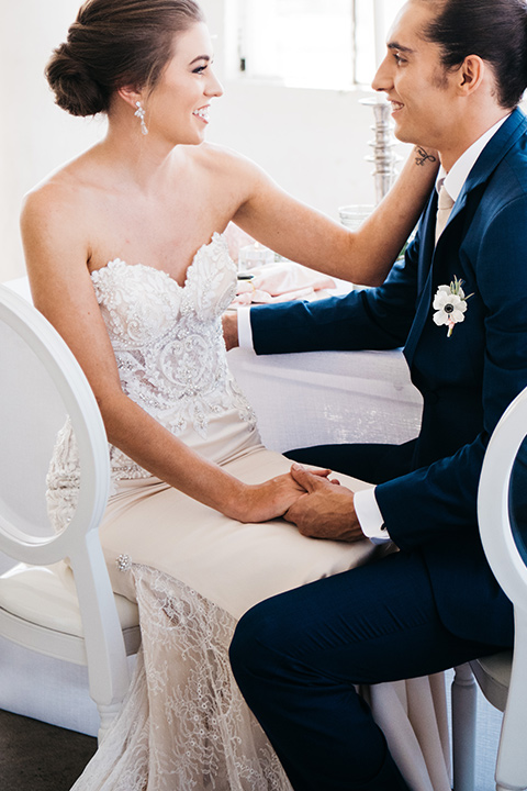 FD-Studios-bride-and-groom-sitting-bride-wearing-a-flowing-strapless-gown-with-a-lace-bodice-groom-in-a-dark-blue-suit-with-a-blush-long-tie