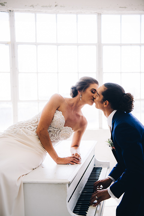 FD-Studios-kissing-on-the-paino-bride-wearing-a-flowing-strapless-gown-with-a-lace-bodice-groom-in-a-dark-blue-suit-with-a-blush-long-tie