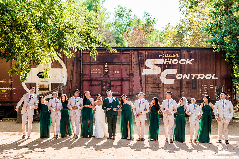 Real-wedding-lani-and-ryan-all-the-bridal-party-arms-linked-and-laughing-groomsmen-in-tan-suits-with-floral-ties-and-brown-shoes-groom-in-green-suit-with-a-floral-tie-and-brown-shoes-bridesmaids-are-in-dark-green-dresses-with-lace-detailing-and-halter-nekline-bride-in-a-lace-a-line-dress-with-hair-in-a-bun-and-long-veil
