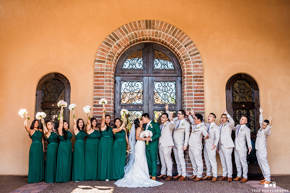 Real-wedding-lani-and-ryan-bridal-party-by-terrecotta-wall-groomsmen-in-tan-suits-with-floral-ties-and-brown-shoes-groom-in-green-suit-with-a-floral-tie-and-brown-shoes-bridesmaids-are-in-dark-green-dresses-with-lace-detailing-and-halter-nekline-bride-in-a-lace-a-line-dress-with-hair-in-a-bun-and-long-veil