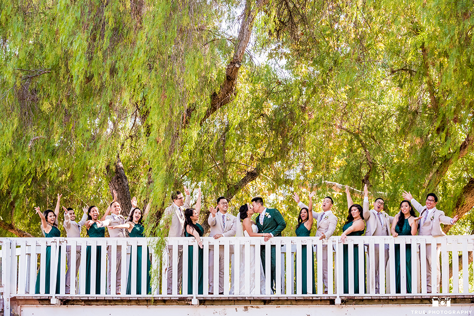Real-wedding-lani-and-ryan-bridal-party-on-white-bridge-bride-and-groom-kissing-groomsmen-in-tan-suits-with-floral-ties-and-brown-shoes-groom-in-green-suit-with-a-floral-tie-and-brown-shoes-bridesmaids-are-in-dark-green-dresses-with-lace-detailing-and-halter-nekline-bride-in-a-lace-a-line-dress-with-hair-in-a-bun-and-long-veil