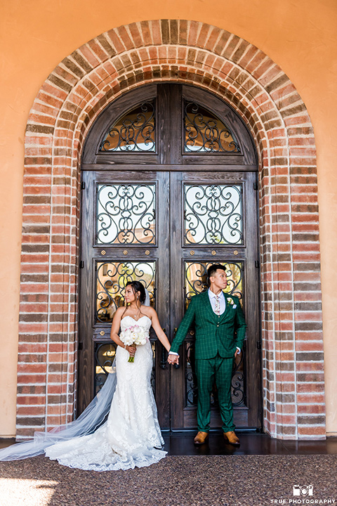Real-wedding-lani-and-ryan-bride-and-groom-holding-hands-facing-away-from-each-other-groom-in-green-suit-with-a-floral-tie-and-brown-shoes-bride-in-a-lace-a-line-dress-with-hair-in-a-bun-and-long-veil