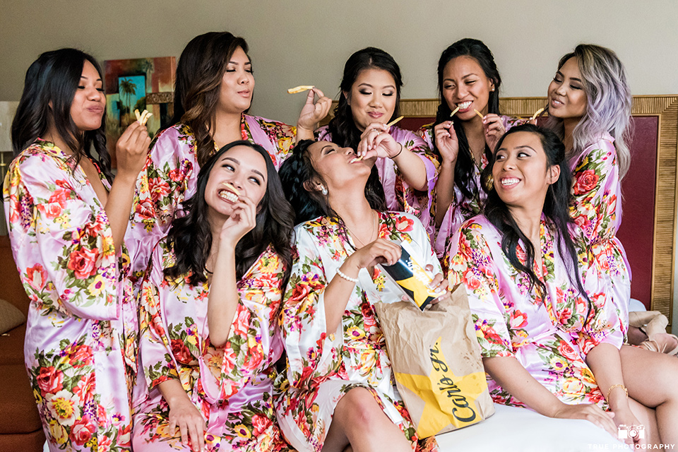 Real-wedding-lani-and-ryan-brideamaids-with-french-fries-bridemaids-in-pink-floral-robes-eating-carls-jr-french-fries-all-laughing-and-smiling