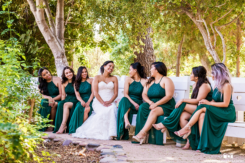 Real-wedding-lani-and-ryan-bridemaids-sitting-on-benches-looking-at-bride-bridesmaids-are-in-dark-green-dresses-with-lace-detailing-and-halter-nekline-bride-in-a-lace-a-line-dress-with-hair-in-a-bun-and-long-veil