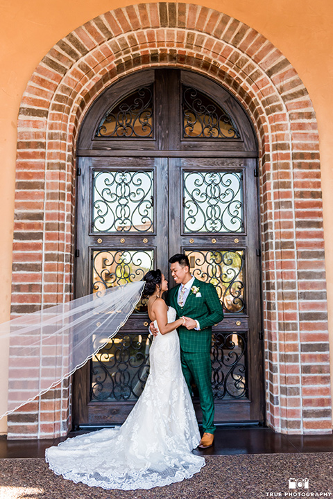 Real-wedding-lani-and-ryan-by-brick-wall-looking-at-each-other-groom-in-green-suit-with-a-floral-tie-and-brown-shoes-bride-in-a-lace-a-line-dress-with-hair-in-a-bun-and-long-veil