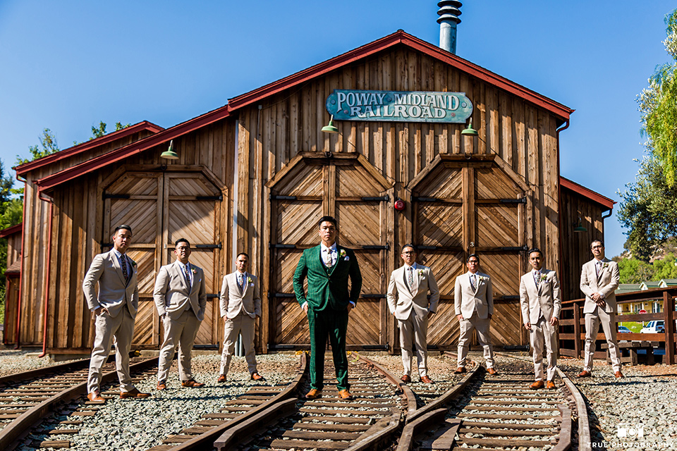 Real-wedding-lani-and-ryan-groomsmen-and-groom-standing-with-hands-in-pocket-in-front-of-train-depot-groomsmen-in-tan-suits-with-floral-ties-and-brown-shoes-groom-in-green-suit-with-a-floral-tie-and-brown-shoes