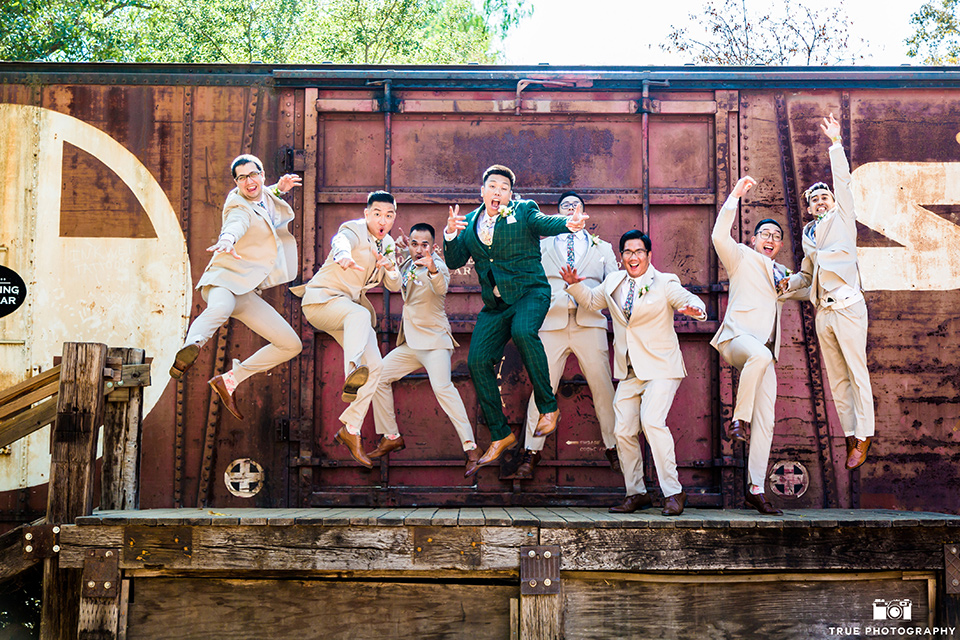 Real-wedding-lani-and-ryan-groomsmen-jumping-by-train-car-groomsmen-in-tan-suits-with-floral-ties-and-brown-shoes-groom-in-green-suit-with-a-floral-tie-and-brown-shoes