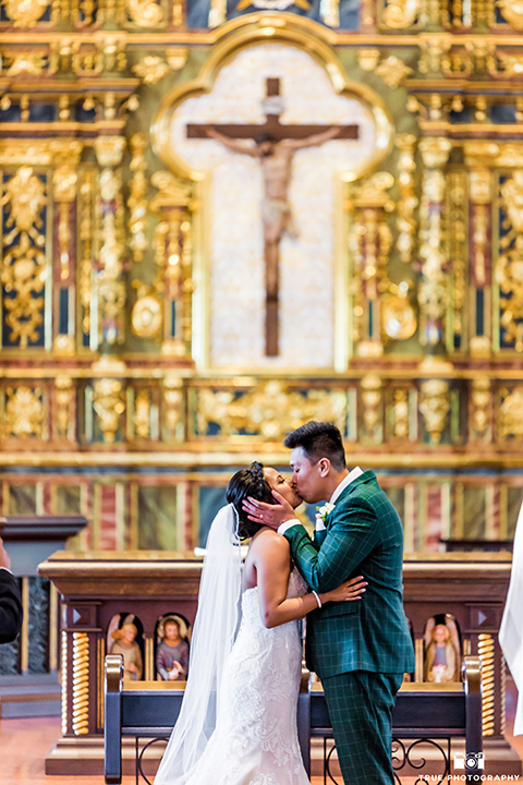 Real-wedding-lani-and-ryan-kissing-in-the-church-his-hands-on-her-face-groom-in-green-suit-with-a-floral-tie-and-brown-shoes-bride-in-a-lace-a-line-dress-with-hair-in-a-bun-and-long-veil