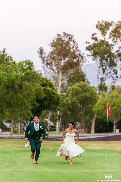 Real-wedding-lani-and-ryan-running-on-the-gold-course-groom-in-green-suit-with-a-floral-tie-and-brown-shoes-bride-in-a-lace-a-line-dress-with-hair-in-a-bun-and-long-veil