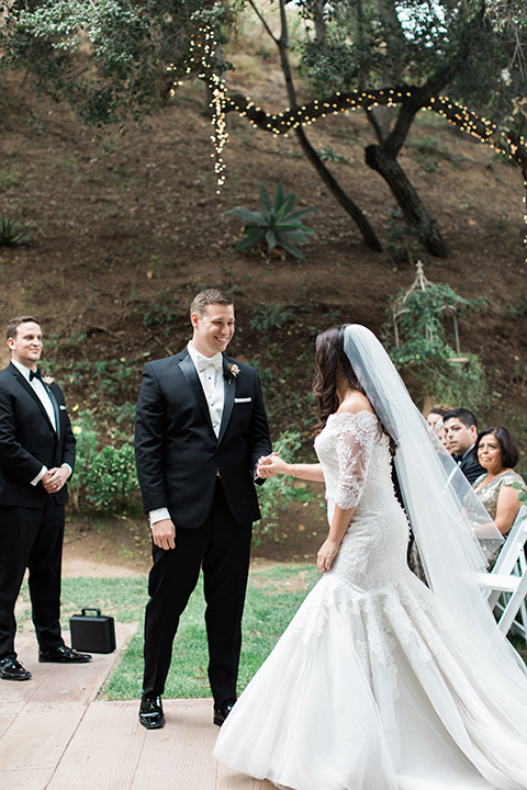los-willows-wedding-bride-and-groom-beginning-ceremony-bride-alone-final-bride-in-a-tulle-ballgown-with-sleeves-groom-in-a-traditional-black-tuxedo-with-black-bow-tie-and-tux-shoes