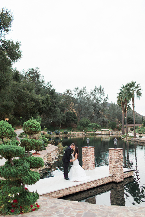 los-willows-wedding-bride-and-groom-kissing-on-dock-bride-alone-final-bride-in-a-tulle-ballgown-with-sleeves-groom-in-a-traditional-black-tuxedo-with-black-bow-tie-and-tuxed-shoes