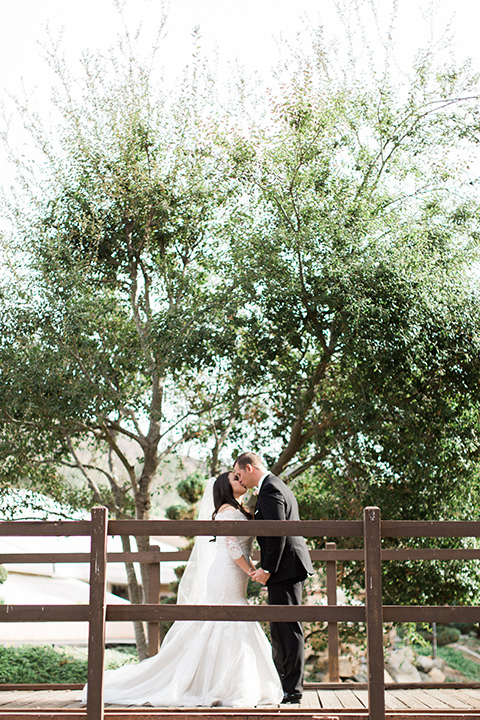 los-willows-wedding-bride-and-groom-on-bridge-bride-in-a-tulle-ballgown-with-sleeves-groom-in-a-traditional-black-tuxedo-with-black-bow-tie-and-tuxed-shoes