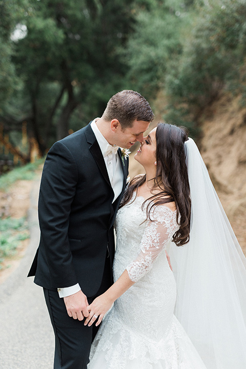 los-willows-wedding-bride-and-groom-standing-by-kissing-bride-in-a-tulle-ballgown-with-sleeves-groom-in-a-traditional-black-tuxedo-with-black-bow-tie-and-tuxed-shoes
