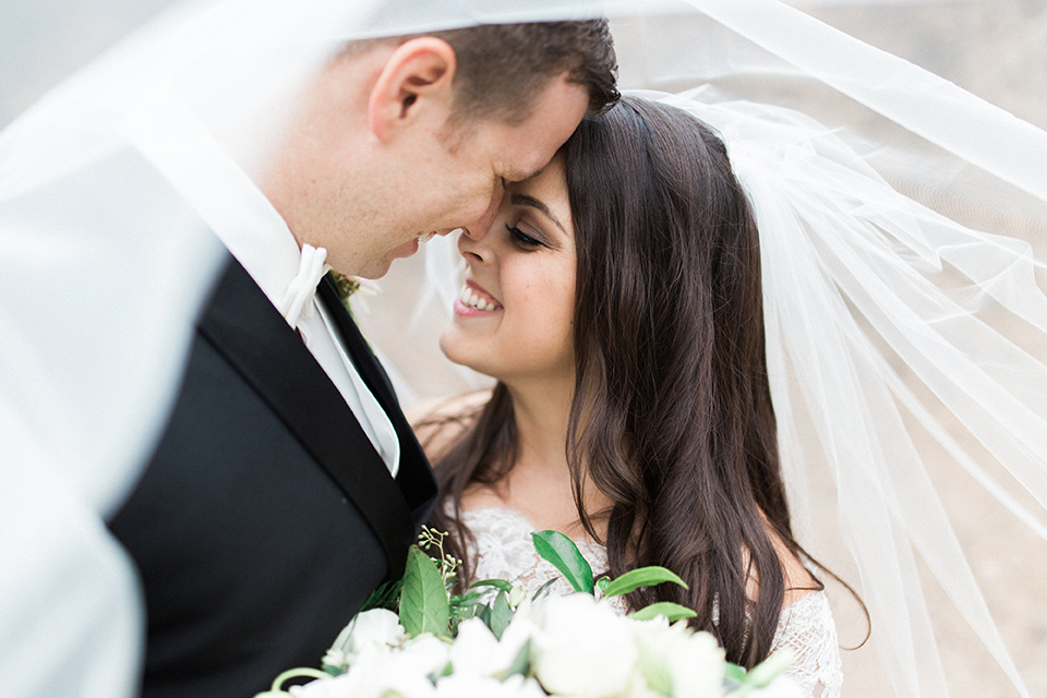 los-willows-wedding-bride-and-groom-under-veil-bride-in-a-tulle-ballgown-with-sleeves-groom-in-a-traditional-black-tuxedo-with-black-bow-tie-and-tuxed-shoes