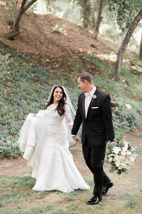 los-willows-wedding-bride-and-groom-walking-bride-in-a-tulle-ballgown-with-sleeves-groom-in-a-traditional-black-tuxedo-with-black-bow-tie-and-tuxed-shoes
