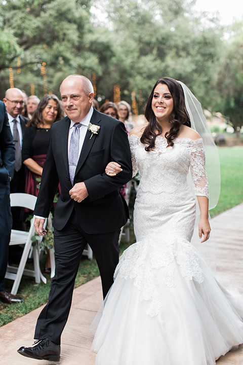 los-willows-wedding-bride-walking-down-aisle-bride-in-a-tulle-ballgown-with-sleeves-groom-in-a-traditional-black-tuxedo-with-black-bow-tie-and-tuxed-shoes