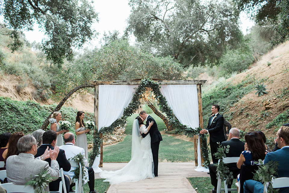 los-willows-wedding-ceremony-firsr-kiss-bride-in-a-tulle-ballgown-with-sleeves-groom-in-a-traditional-black-tuxedo-with-black-bow-tie-and-tuxed-shoes