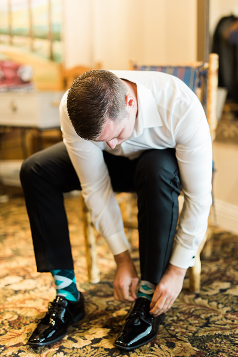 los-willows-wedding-groom-tying-shoes-groomsmen-in-a-traditional-black-tuxedo-with-black-bow-tie-and-tuxed-shoes