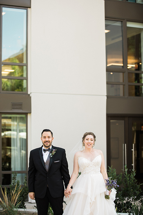 Avenue-of-the-arts-wedding-bride-and-groom-facing-camera-in-front-of-building-bride-in-tulle-ball-gown-with-beaded-bodice-and-beaded-headband-groom-inblack-tuxedo-with-a-silver-vest-and-silver-bowtie