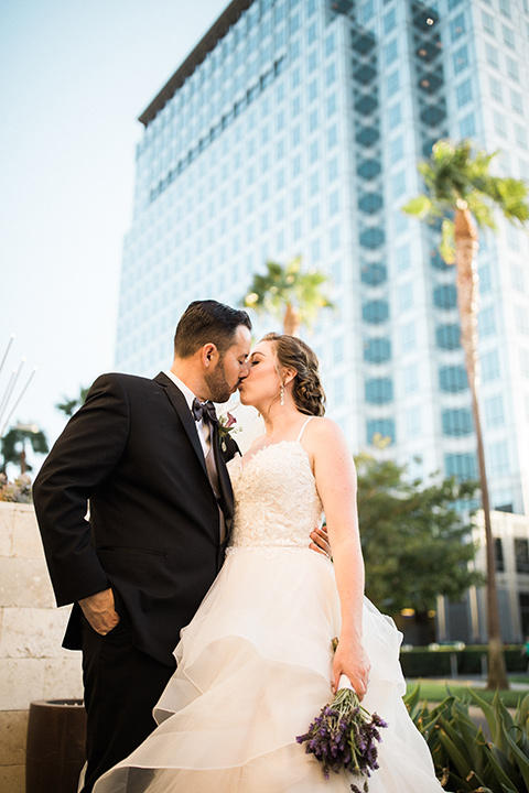 Avenue-of-the-arts-wedding-bride-and-groom-with-tall-buildings-behind-the-bride-in-tulle-ball-gown-with-beaded-bodice-and-beaded-headband-groom-inblack-tuxedo-with-a-silver-vest-and-silver-bowtie